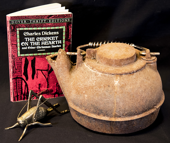 photo of a Charles Dickens book, a kettle and a brass cricket