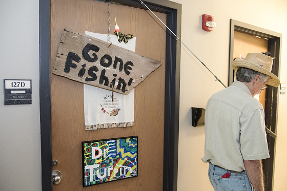 Tom Turpin leaving his office, carrying a fishing pole