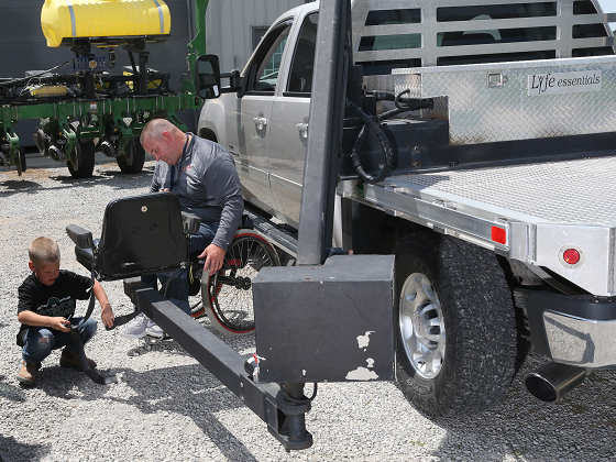 Justin Hosler and his son, Jacob, prepare a pickup-mounted lift chair so that Hosler can reach his t