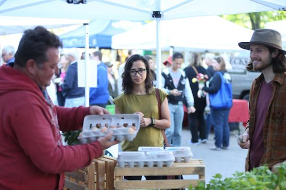 Farmer's Market vendor showing customer a dozen eggs