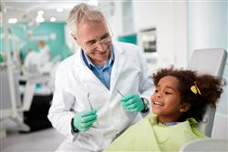 dentist preparing to clean child's teeth