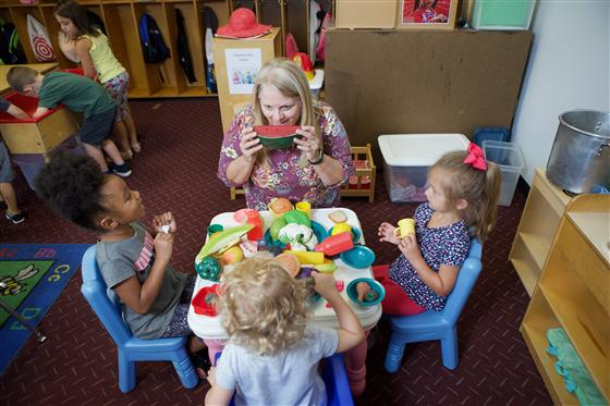 Woman engaging in educational and fun, hands-on activities with three children.