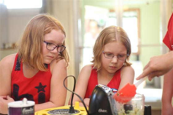 Two girls learn from a cooking demonstration.