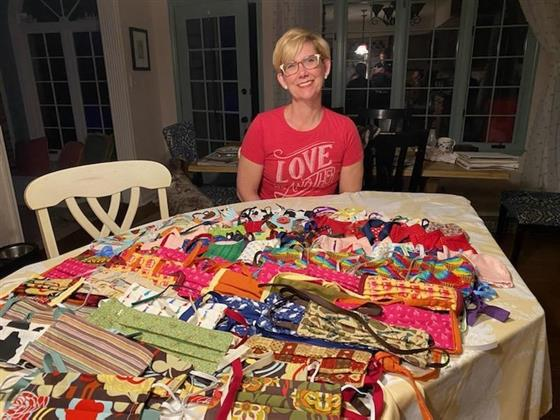 4-H club leader displays many homemade face masks that she sewed for her local community