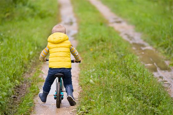 Child rides bike on path.