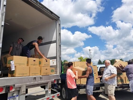 Community members unload a truck of food boxes to distribute to agencies and pantries in Fayette Cou
