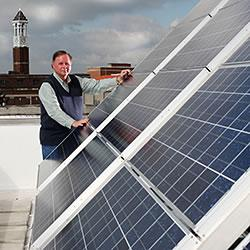 Wally Tyner amid solar panels on the roof of Purdue's Knoy Hall. (Purdue Agricultural Communication