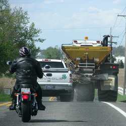 photo of a large farm vehicle on road with other drivers